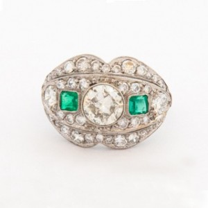 An Art Deco Emerald and Diamond Cluster Ring featuring a central early round brilliant cut diamond with a square emerald cut emerald on each shoulder all surrounded by pave set round brilliant cut diamond.