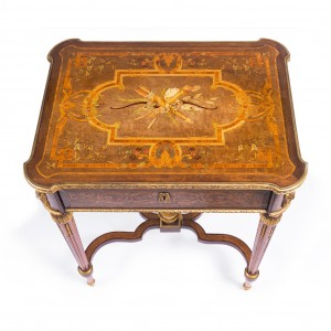 "An exceptional 19th century French Napoleon III occasional table signed 'Tahan Paris'. The top beautifully inlaid and cross-banded with a romantic panel inlaid with a bow and a quiver of arrows, bound in flowers, bordered by flowers, leaves and ribbons, sits over an inlaid frieze supported on turned fluted legs joined with a stretcher. The top lifts to reveal fine rosewood compartments for jewellery or other small articles. Note the fine quality of this piece is evidenced by the chaste gilded hinges. Footnote: Alphonse Tahan (1830-1880) was the official ébéniste de l'Empereur or master cabinet maker to Emperor Napoleon III and his wife, the Empress Eugenie. Born in Belgium in 1830, he had opened a shop at 30 Rue de la Paix in the heart of Paris by the age of 19. Tahan grew to prominence as a craftsman known for creating beautiful and varied pieces, from the elaborate to the simple. His work, combined a classical formality reminiscent of the late 1700s and the subject of his motifs borrowed from the Louis XVI taste. Tahan eventually caught the eye of Napoleon's wife, Empress Eugenie, and he became the official ""ebeniste"" (cabinetmaker) to the Emperor and his wife. The Empress was considered a trend-setter; a great beauty herself, she had an eye for things that were aesthetically pleasing. Her regard for Tahan's workshop led to great demand for his furniture and smaller items, such as this table. His pieces became sought after by the upper echelons of Paris society. He moved his shop to Boulevard des Italiens in 1978, but died a short two years later. His works were in demand right across Europe, where they are awarded medals exhibiting at The London Crystal Palace Exhibition in 1851, and the Paris Exposition Universelle in 1855."