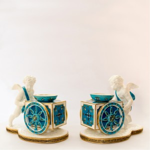 Pair Moore Brothers candlesticks in the form of cupids pushing wheelbarrows. Retailed by Thomas Goode, c. 1880.