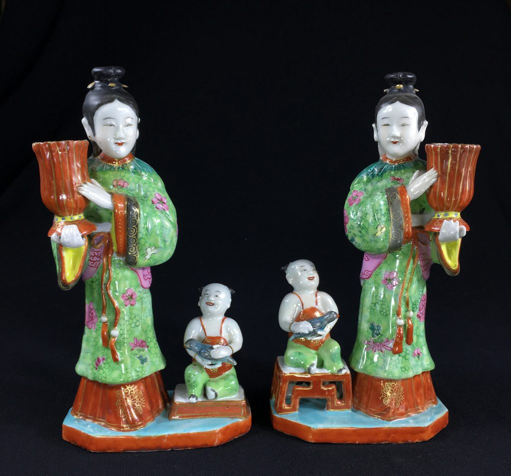 Moorabool Antiques Rare pair of Chinese porcelain candlestick figures, each modelled as a maiden holding a red vase-shaped candle sconce, a seated child at her side holding a turquoise parrot, their clothing coloured in green & red ground with with gilt flowers, her coat with famille rose flowerheads and a fine collar of peacock feathers, the whole set on an octagonal slab base coloured in turquoise with red edge. Qianglong, circa 1780. Size: 23cm high